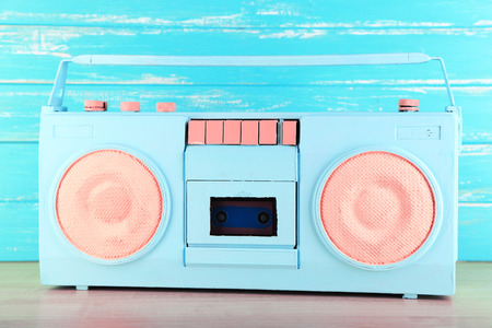 Colorful retro radio, on blue wooden background photo