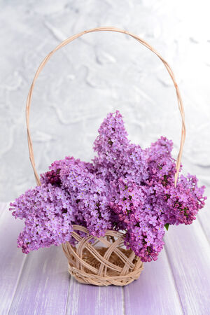 Beautiful lilac flowers in wicker basket on table on light background photo