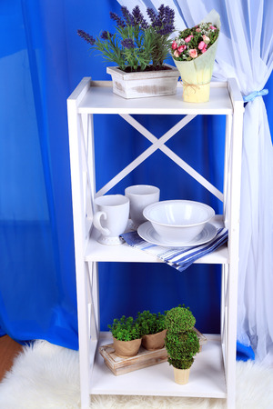Beautiful white shelves with tableware and decor on color background photo