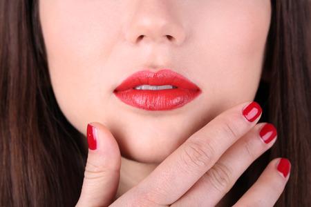 Red lips and nails closeup photo