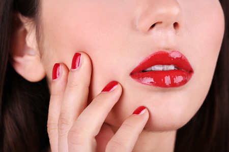 Red lips and nails closeup photo