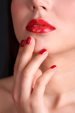 Girl with red lips and nails on dark background photo