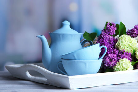 Composition with tea set and bouquet of beautiful spring flowers on tray, on wooden table, on bright background photo