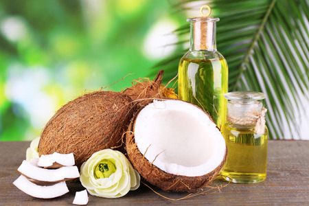 Coconuts and coconut oil on wooden table, on nature background Stock Photo