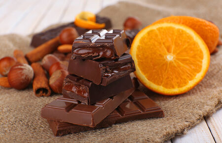 Chocolate, orange and nuts on table photo