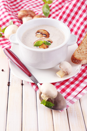 Mushroom soup in white pot, on napkin, on wooden background photo