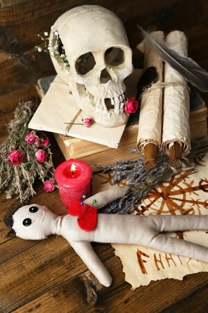 Conceptual photo of love magic. Composition with skull, voodoo doll, dried herbs and candle on  dark wooden background photo