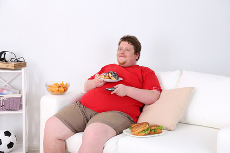 Lazy overweight male sitting with fast food on couch and watching television Archivio Fotografico - 98214964