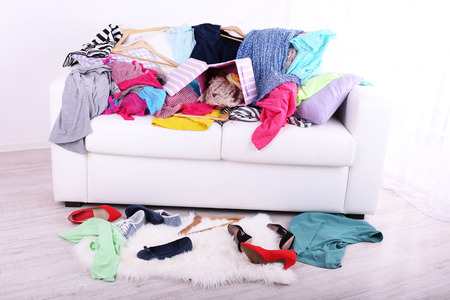 Messy colorful clothing on sofa on light background Stock fotó