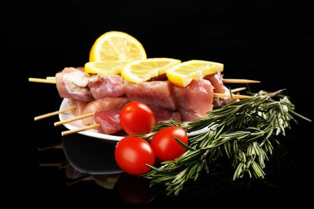 Raw pork kebab on black background photo