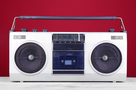Retro cassette stereo recorder on table on red background photo