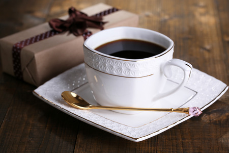 decaffeinated: Cup of coffee and gift on wooden table close-up Stock Photo