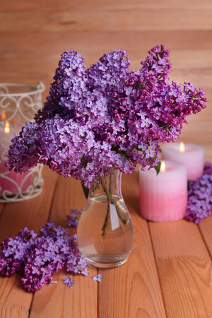 Beautiful lilac flowers in vase on table on wooden background photo