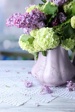 Composition with tea mugs and beautiful spring flowers in vase, on wooden table, on bright background photo