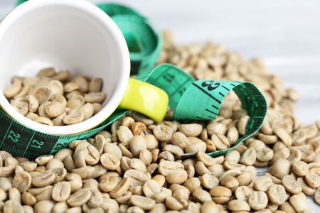 unprocessed: Raw green coffee beans and measuring tape, on color wooden background. Concept of weight loss