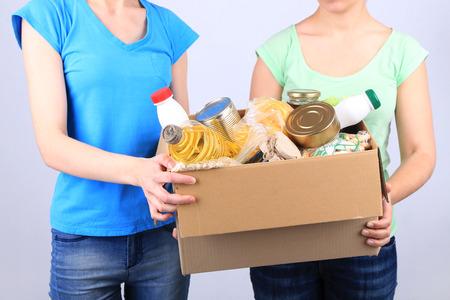 Freiwillige mit Spendendose mit Lebensmitteln auf grauem Hintergrund