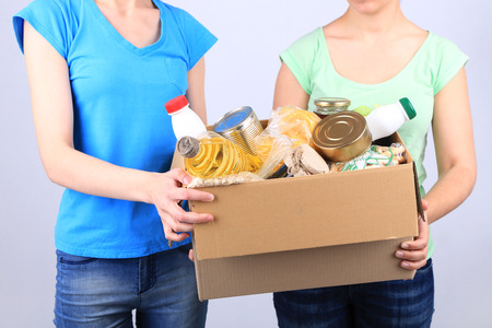 produits alimentaires: Volontaires avec boîte de dons avec les denrées alimentaires sur fond gris