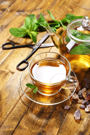 Composition of fresh mint tea in glass cup and teapot  on wooden background photo
