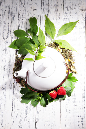 Herbal natural tea in teapot with dry flowers and herbs ingredients, on color wooden background photo