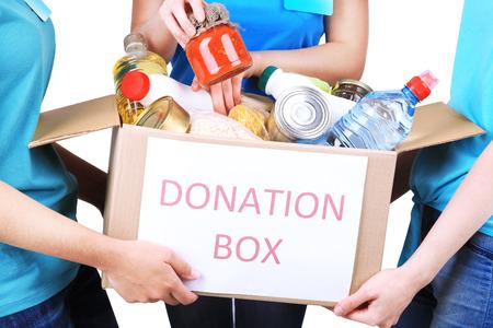 Volontaires avec boîte de dons avec des denrées alimentaires sur fond gris