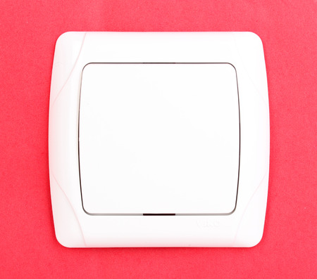 push room: Modern light switch on red background Stock Photo