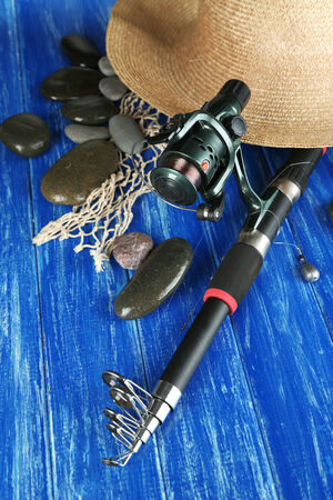 gumboots: Fishing rod, gumboots and hat on wooden table close-up