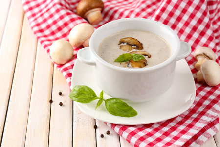Mushroom soup in white pot, on napkin, on wooden background Stock Photo - 28761480