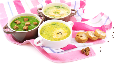 Tasty soup in saucepans, isolated on white photo