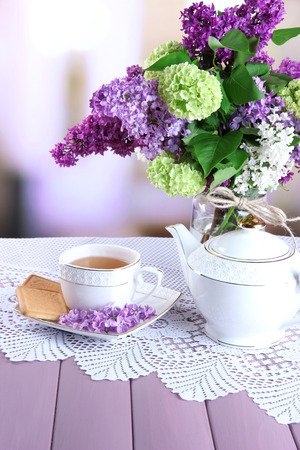 Composition with teapot,  mug and beautiful spring flowers in vase, on wooden table, on bright background photo