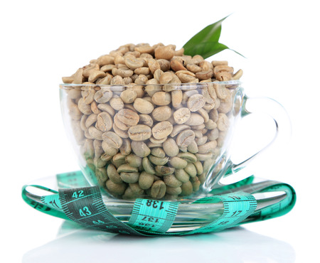Raw green coffee beans in glass cup and measuring tape, isolated on white. Concept of weight loss photo