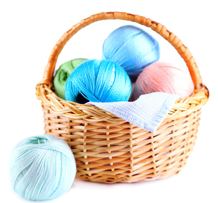 basket embroidery: Colorful yarn balls for knitting in wicker basket, isolated on white