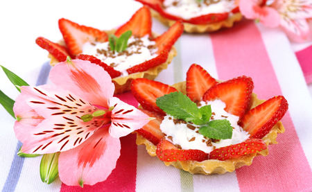 Tasty tartlets with strawberries on table close-up photo