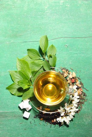 Glass cup with dry flowers and herbs ingredients for tea, on color wooden background photo