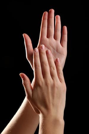 manos aplaudiendo: Las manos humanas sobre fondo negro