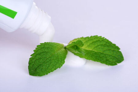 Toothpaste squeezed from tube, mint leaves, close-up, isolated on white photo