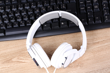 Headphone and keyboard close-up on wooden desk background photo