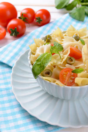 Delicious pasta with tomatoes on plate on table close-up photo