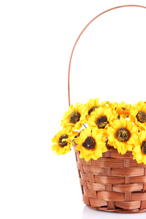 Bouquet of beautiful artificial flowers in wicker basket, isolated on white photo