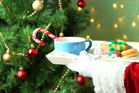 Santa holding mug and plate with cookies in his hand, on bright background photo