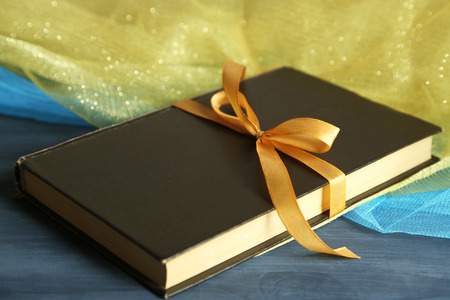 Book wrapped with color ribbon, on wooden background photo