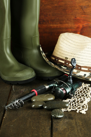 ardour: Fishing rod, gumboots and hat on wooden table close-up