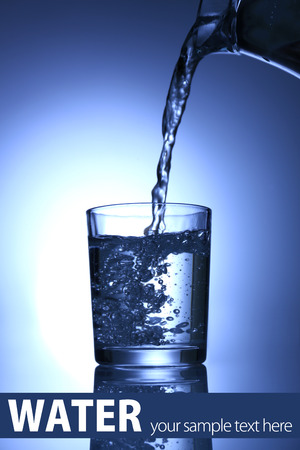 Pour water from  pitcher into  glass, on dark blue background photo