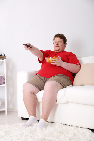 Lazy overweight male sitting on couch with chips and watching television Stock Photo