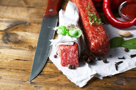 Tasty salami sausage and spices on wooden background photo