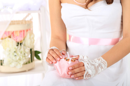 wrist cuffs: Bride in white dress and gloves holding decorative pillow with wedding rings, close-up, on light background