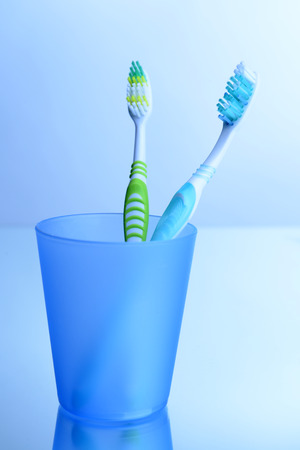 Toothbrushes in glass on light grey background photo