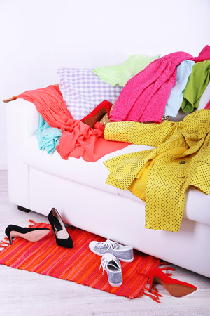Messy colorful clothing on  sofa on light background photo