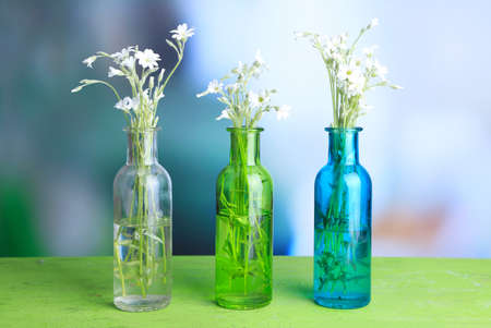 White wildflowers in bottles on wooden table, on light background photo
