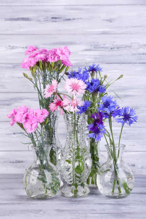 Beautiful summer flowers in vases on grey wooden background photo