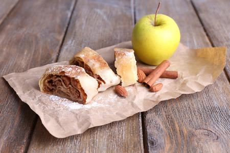 Tasty homemade apple strudel  on paper napkin, on wooden background photo